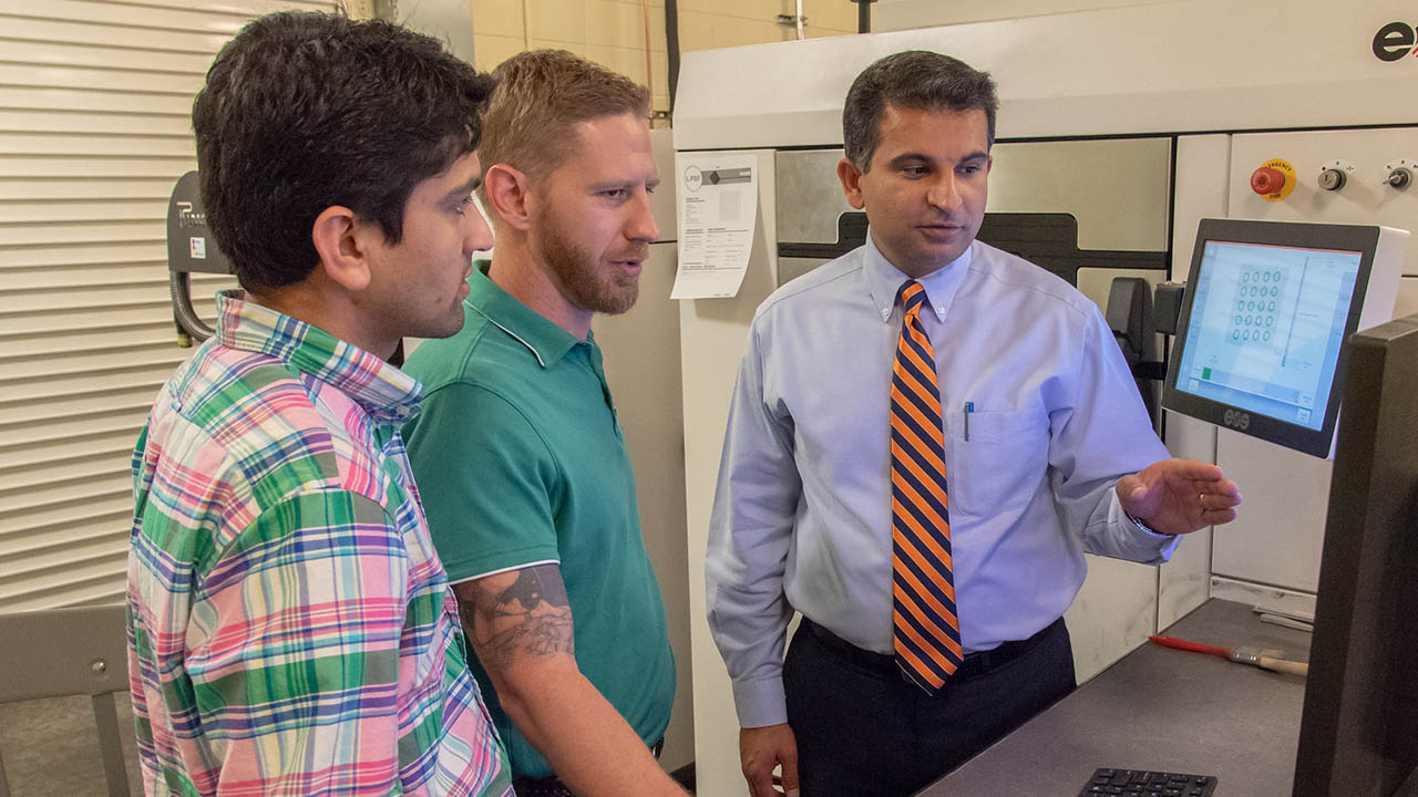 (Shown from left) Mechanical engineering doctoral students Basil Paudel and Jonathan Pegues look at a 3-D computer-aided design model with Nima Shamsaei, director of the National Center for Additive Manufacturing Excellence, in the additive manufacturing lab in Wiggins Hall at Auburn University.